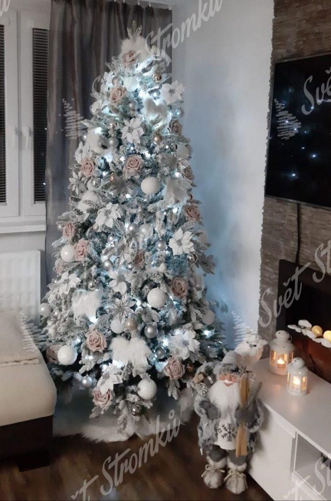 Bílý vánoční stromek ozdobený bílými květy a koulemi.