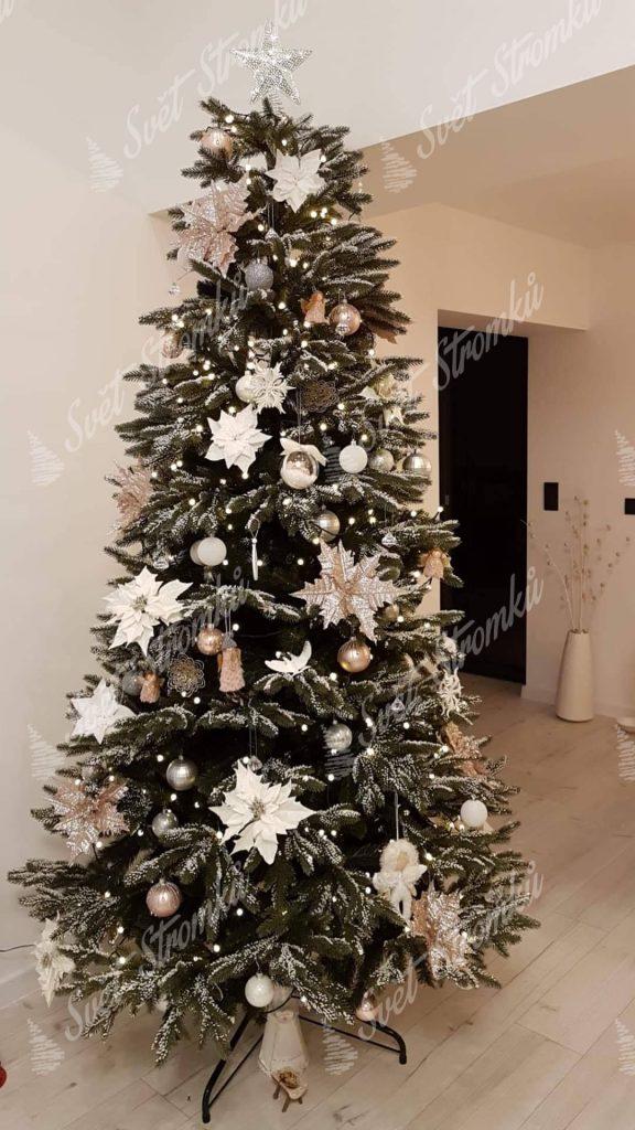 Zasněžený vánoční stromek 3D ozdobený bílými květy a zlatými koulemi.