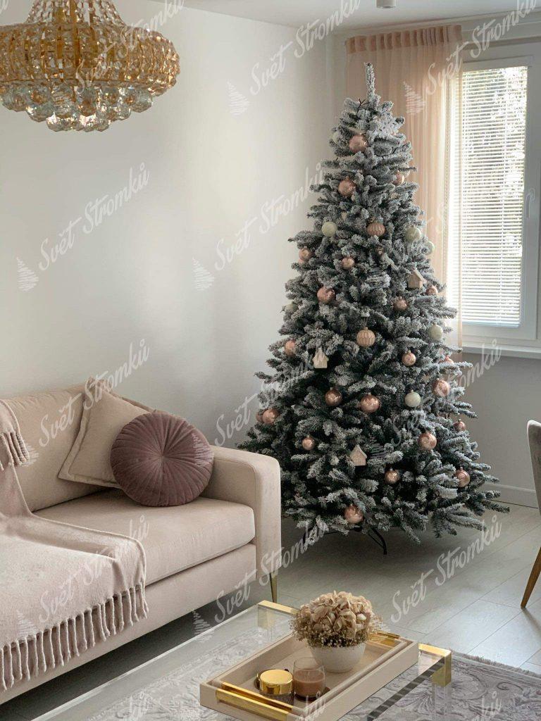 Zasněžený vánoční stromek ozdobený zlatými a pudrovými vánočními ozdobami.