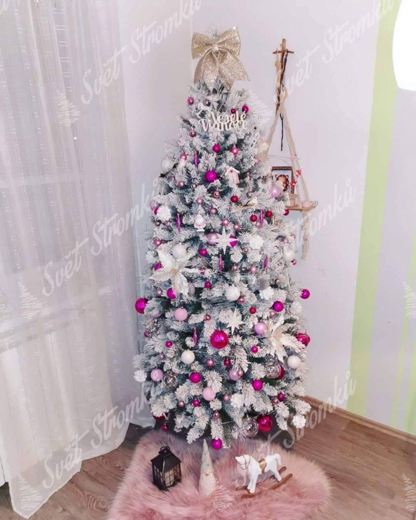 Bílý vánoční stromek ozdobený růžovými a bílými koulemi spolu s bílými hvězdičkami.
