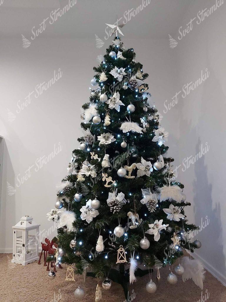 Zelený vánoční stromek ozdobený bílými květy, šiškami a andělskými křídly.