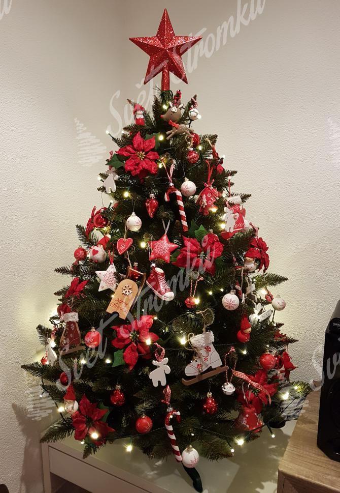 Zelený vánoční stromek smrk ozdobený červenými květy a hvězdičkami.