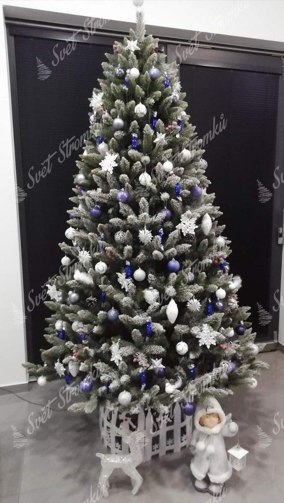 Vánoční stromek s jemně zasněženými konečky větviček ozdobený bílými a modrými vánočními ozdobami.