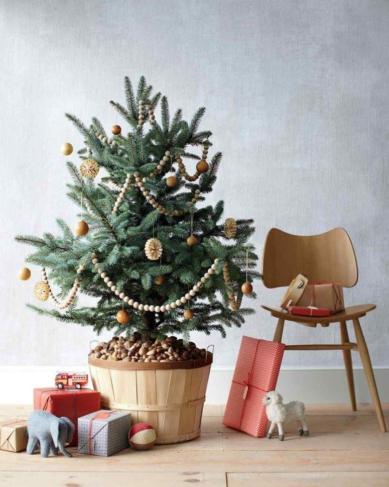 Živý vánoční stromek v květináči ozdobený dřevěnými ozdůbky a řetězem. Vedle květináče jsou naskládané dárky