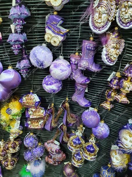 Fialové vánoční ozdoby na stromeček ve tvaru bot, královských korun, bot na podpatku a karnevalových masek.