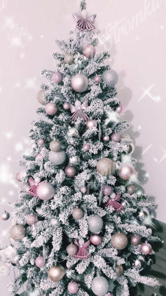 Bílý vánoční stromek zdobený stříbrnými a růžovými koulemi.