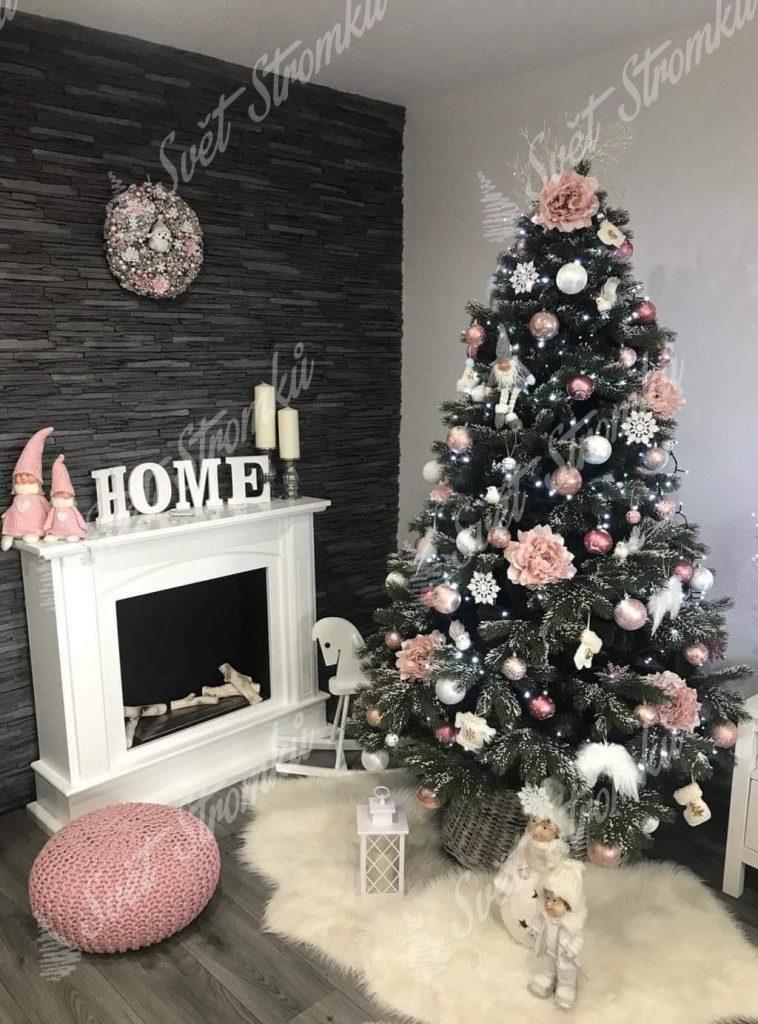 Zelený vánoční stromeček se zasněženými konečky větviček u krbu. Stromek ozdobený narůžovělými květy a bílými andělskými křídly.