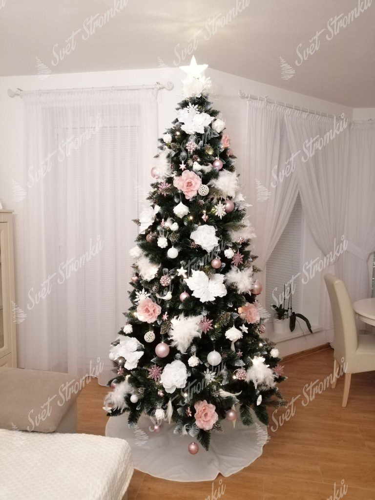 Zelený vánoční stromeček ozdobený bílými vánočními květy a bledě růžovými růžemi.