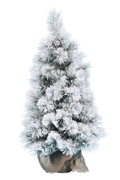 Na obrázku je malý, huňatý stromek cely pokrytý umělým sněhem. Stromek stoji na umělém podstavci zabaleném v pytlovině.