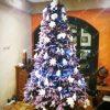 Fialový vánoční stromek ozdobený bílými květy a vánočními ozdobami