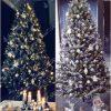 Ozdobený zasněžený bílý vánoční stromeček bílými a modrými vánočními ozdobami.