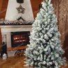 Bílý vánoční stromek ve vánočně vyzdobené místnosti s krbem.