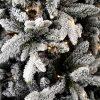 Detailní fotka větviček vánočního stromku zasněžených do bílá