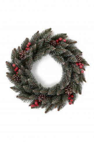 Pohled shora na vánoční věnec tyrkysové zelené barvy doplněn šiškami s borovice a červenými lesními plody.
